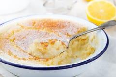 Zitronenpuddingkuchen mit frischen Zitronen auf einem weißen hölzernen Hintergrund Lizenzfreies Stockfoto