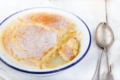 Zitronenpuddingkuchen mit frischen Zitronen auf einem weißen hölzernen Hintergrund Lizenzfreie Stockfotografie