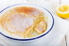 Zitronenpuddingkuchen mit frischen Zitronen auf einem weißen hölzernen Hintergrund Stockfoto