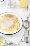 Zitronenpuddingkuchen mit frischen Zitronen Hölzerner Hintergrund Stockfotos