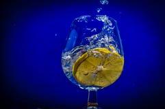 Zitronenscheibe fällt in ein Glas Wasser Stockfoto