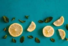 Zitronenscheiben und tadellose Kräuter gegen blauen Hintergrund mit copyspace Draufsicht von Zitronen und von Blättern lizenzfreie stockfotografie