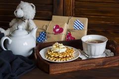 Zitronentee, Waffeln mit Eiscreme, Honig und Nüsse in einem Weinlesebehälter, selbst gemachte Valentinstaggeschenke im Kraftpapie lizenzfreies stockfoto