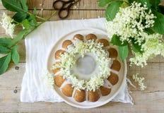 Zitronentorte mit einer Glasur des Zuckers und elderflower süßen mit Sirup, verziert mit Holunderbeerblumen Rustikale Art lizenzfreie stockbilder