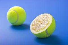 Zitronetenniskugeln auf blauem Hintergrund Stockfotografie