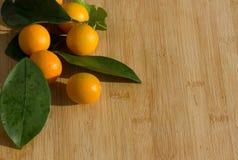 Zitrusfrüchte auf hölzernem Küchenbrett und -blättern Stockfoto