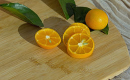 Zitrusfrüchte auf hölzernem Küchenbrett und -blättern Lizenzfreie Stockfotos