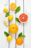 Zitrusfrüchte (Zitrone, Pampelmuse und Orange) auf weißem Holz Stockfotos