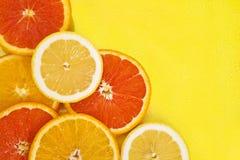 Zitrusfruchtscheiben auf einem gelben Hintergrund Lizenzfreie Stockbilder