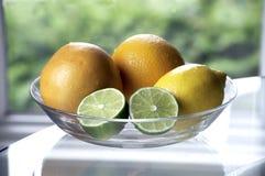 Zitrusfrucht in einer Schüssel mit Kalk-Hälften Stockfotos
