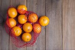 Zitrusfrucht-Tangerine in den Orangen im Plastiknettotaschenpaket Kein Plastikkonzept Verpacken, das nicht aufbereitet plastik Ru stockbilder