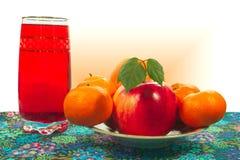 Zitrusfrucht und Apfel auf einer Platte, ein Glas Saft Stockfoto