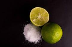 Zitrusfruchtkalkfrucht halb auf schwarzem Hintergrund, kleine grüne Zitronen mit Salz Lizenzfreie Stockbilder