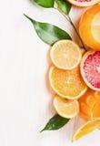 Zitrusfruchtsaft und geschnittene Früchte: Orange, Zitrone und Pampelmuse auf weißem hölzernem Lizenzfreie Stockfotografie