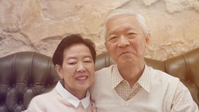 Zitten de hogere ouders van Rich Asian in backgrou van het luxe mooie huis royalty-vrije stock afbeelding