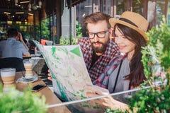 Zitten de de Interester jonge man en vrouw en bekijken kaart die zij heeft gehouden Vrouwenglimlachen De kerel is ernstig Zij heb royalty-vrije stock afbeeldingen