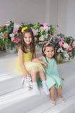 Zitten de mooie meisjes in gele en turkooise kleding dichtbij bloemen in een studio Royalty-vrije Stock Fotografie
