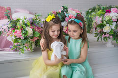 Zitten de mooie meisjes in gele en turkooise kleding en kijken aan het stuk speelgoed konijn in een studio stock fotografie