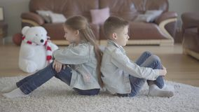 Zitten het de portret tweeling Kaukasische jongen en meisje op de vloer van woonkamer rijtjes boos aan elkaar Broer en stock video