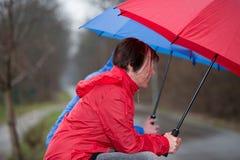 Zittend in de Regen, door een paraplu wordt behandeld die Royalty-vrije Stock Fotografie