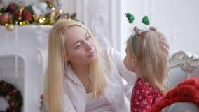 Zittend op de laag door de open haard met een Kerstmisdecor, de vrouw en haar heeft weinig dochter pret het babbelen stock videobeelden