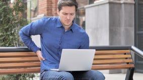 Zittende openlucht jonge mens die met rugpijn aan laptop werken stock video
