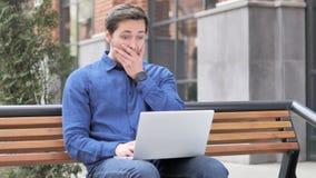 Zittende openlucht jonge mens die in schok aan laptop werken stock footage