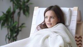 Zitternde Frau, die auf dem Stuhl bedeckt mit dem Plaid sich fühlt kalt sitzt stock video