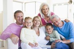 Zitting die van de familie de binnen glimlacht Royalty-vrije Stock Foto's