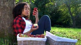 Zitting die van de tiener de jonge vrouw tegen een boom in een boomgaard leunen die een appel eten die een celtelefoon voor socia stock video
