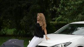 Zitting van de blonde de jonge vrouw op de kap van de witte auto in de zomerdag Langzame Motie stock footage