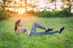 Zitting van de geschiktheids de aantrekkelijke jonge vrouw op het gras in een park Stock Afbeelding