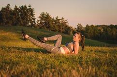 Zitting van de geschiktheids de aantrekkelijke jonge vrouw op het gras in een park Royalty-vrije Stock Afbeelding