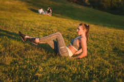 Zitting van de geschiktheids de aantrekkelijke jonge vrouw op het gras in een park Stock Afbeeldingen
