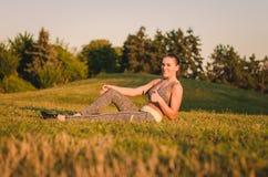Zitting van de geschiktheids de aantrekkelijke jonge vrouw op het gras in het park Royalty-vrije Stock Afbeeldingen