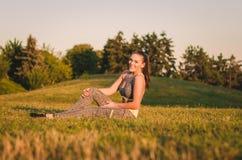 Zitting van de geschiktheids de aantrekkelijke jonge vrouw op het gras in het park Stock Foto