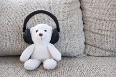 Zitting van de glimlach de witte teddybeer op bank en het dragen van hoofdtelefoon Royalty-vrije Stock Afbeelding