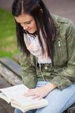 Zitting van de inhouds de donkerbruine student bij de banklezing Stock Foto