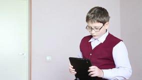 Zitting van de jongens de speeltablet op het bureau stock videobeelden