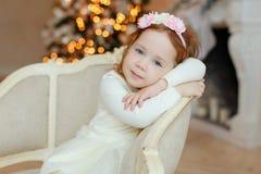 Zitting van de meisje de Krullende baby als voorzitter en droevig bij Kerstmis Royalty-vrije Stock Foto's