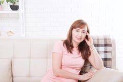 Zitting van de middenleeftijds de mooie vrouw op bank thuis achtergrond Jonge volwassenen Exemplaarruimte en spot omhoog Malplaat Royalty-vrije Stock Foto