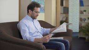 Zitting van de ochtend de rituele, ontspannen mens op laag en lezingskrant thuis stock videobeelden