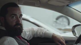 Zitting van de portret de aantrekkelijke zekere gebaarde zakenman in het voertuig in het autohandel drijven Autotoonzaal stock videobeelden