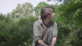 Zitting van de portret de eenzame zenuwachtige jonge mens op de bank in het park die op zijn vriend of meisje wachten De kerel stock footage