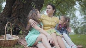 Zitting van de portret de elegante hogere vrouw op het gras onder de boom in het park die twee leuke kleindochters, het vertellen stock video