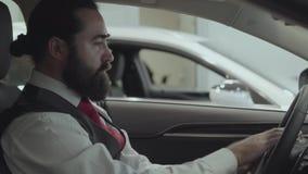 Zitting van de portret inspecteert de aantrekkelijke succesvolle gebaarde zakenman in het voertuig en onlangs gekochte auto van d stock videobeelden