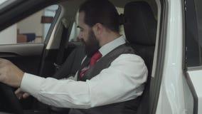 Zitting van de portret inspecteert de aantrekkelijke zekere gebaarde zakenman in het voertuig en onlangs gekochte auto van de aut stock video