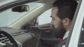 Zitting van de portret inspecteert de aantrekkelijke zekere gebaarde zakenman in het voertuig en onlangs gekochte auto van de aut stock footage