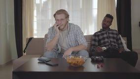Zitting van de portret de knappe gebaarde mens op de bank die door cellphone spreken terwijl zijn Afrikaanse Amerikaanse vriend d stock video