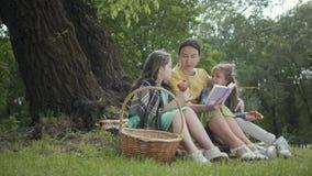 Zitting van de portret de leuke hogere vrouw op de deken onder de boom in het park die het boek lezen Aanbiddelijke twee stock video